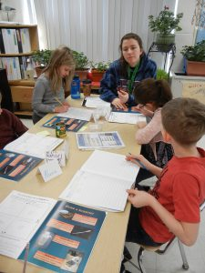 A Williams student helping elementary students complete their BioEYES science journal.