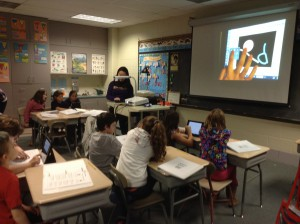 Elementary students learn how to use iPad technology to create illustrations.